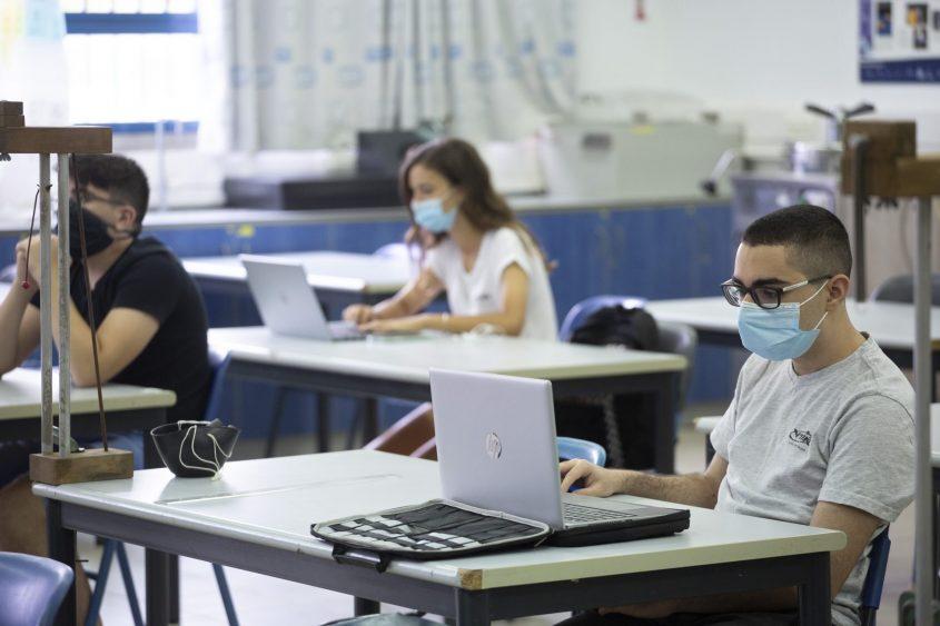 תלמידים לומדים בכיתה עם מסכות עקב משבר הקורונה (צילום: מוטי מילרוד)